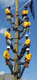 Seven Mishawaka Utilities electrical lineworkers posing atop pole with Indiana flag
